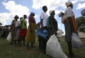صورة من أرشيف رويترز لقرويين من زيمبابوي لدى حصولهم على حصصهم الشهرية من المساعدة الغذائية في مدرسة  بماونت داروين على بعد 254 كيلومترا شمالي هراري.