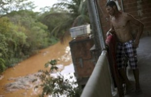رجل برازيلي ينظر  من شرفة منزله الواقع على ضفة نهر بعد انهيار سدين في منطقة مناجم يوم 12 نوفمبر تشرين الثاني 2015. تصوير: ريكاردو موريس - رويترز